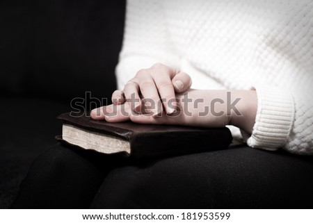 Woman holding hands over her bible and praying to God.