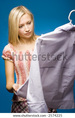 Woman holding hanger with blouse. Examining it's quality. - stock photo