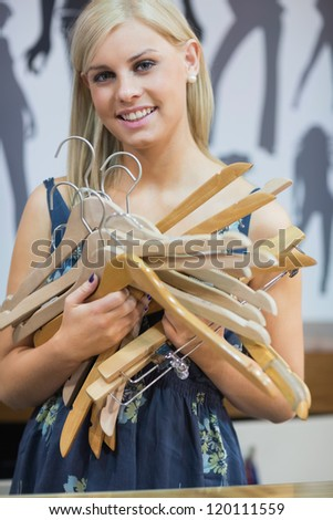 Woman holding hangers and smiling - stock photo