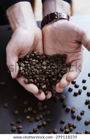 Woman holding heap of fresh coffee beans,  close up
