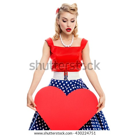 Woman holding heart symbol, dressed in pin-up style dress with polka dot, isolated over white. Caucasian blond model posing in retro fashion and vintage concept studio shoot. - stock photo