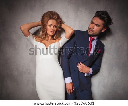 woman holding her hair up next to her boyfriend, he is looking at her in studio