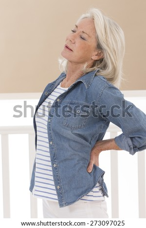 Woman holding her hands on her injured back - stock photo