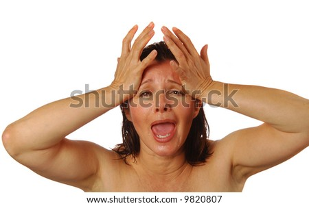 Woman holding her head in agony, shock, or grief - stock photo