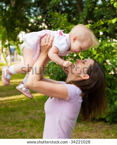 Woman holding her one year old daughter - stock photo