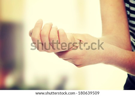 Woman holding her wrist - pain concept - stock photo