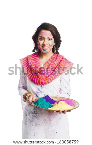 Woman holding Holi colors in a plate - stock photo