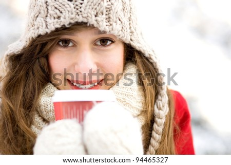 Woman holding hot coffee on winter day - stock photo