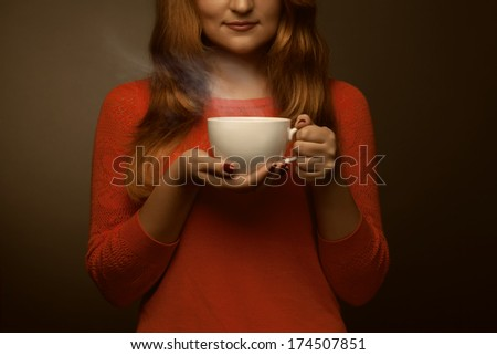 woman holding hot cup and smiles