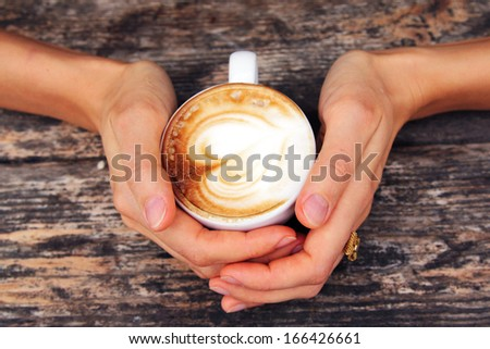 woman holding hot cup of coffee