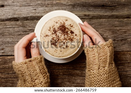 woman holding hot cup of coffee - stock photo