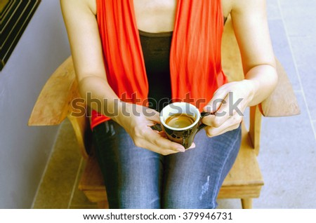 woman holding hot cup of coffee in coffee cafe, vintage filter. - stock photo