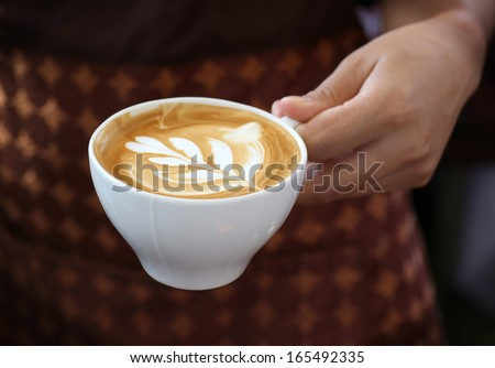 woman holding hot cup of coffee,with leaf - stock photo