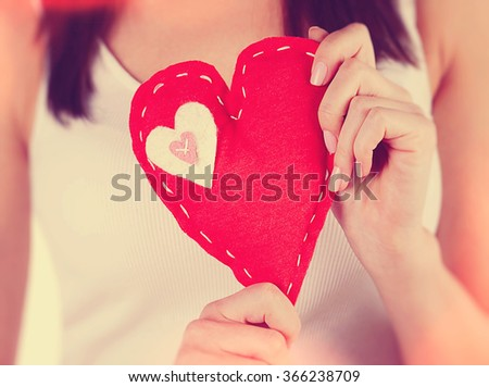 Woman holding in hand red heart shaped soft toy, body part, best handmade present for Valentine day, love concept - stock photo