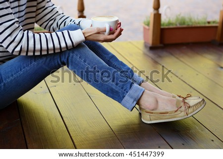 Woman holding in hands cup of coffee with milk sitting on the wooden floor on the terrace - stock photo