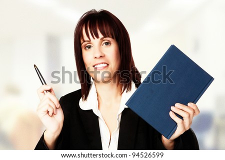 woman holding in one hand a pen and in the other a notebook - stock photo