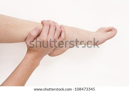 Woman holding injured ankle - stock photo