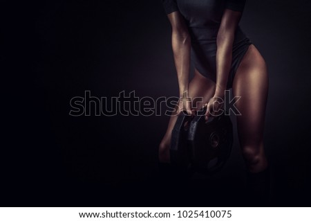 Woman holding iron plates for training