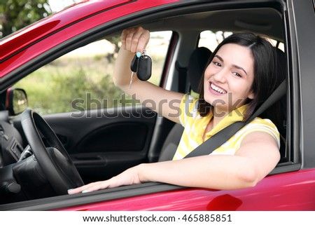 Woman holding key in car