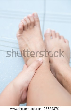 Woman holding left ankle while sitting down to show pain in the ankle area - stock photo