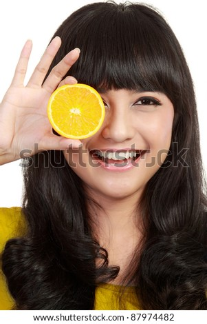 woman holding lemons up to eyes and smiling. in isolated white - stock photo