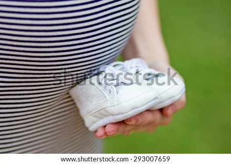 woman holding little baby shoes in front of the pregnant belly. Close up picture of pregnant woman holding a baby shoe - stock photo