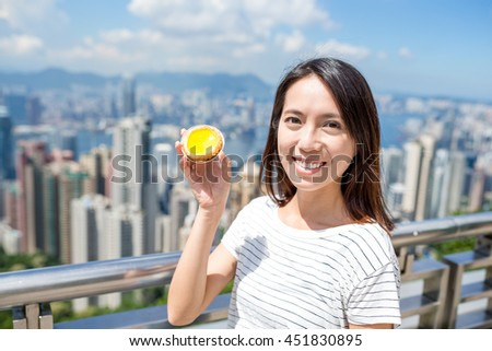 Woman holding local food in Hong Kong, egg tart