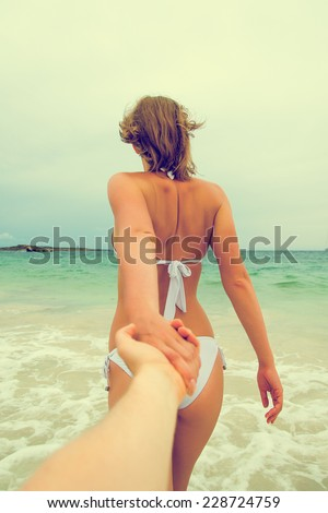 Woman holding man's hand and leads to the sea. Vintage effect. - stock photo
