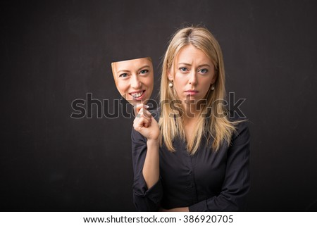 Woman holding mask of her happy face  - stock photo