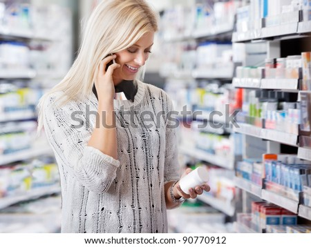 Woman holding medication container while talking on cell phone - stock photo
