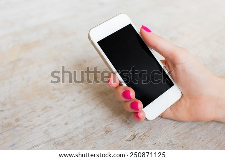 Woman holding mobile phone - stock photo