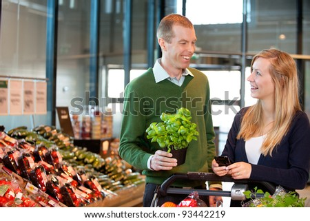 Woman holding mobile phone and looking at man in shopping centre - stock photo