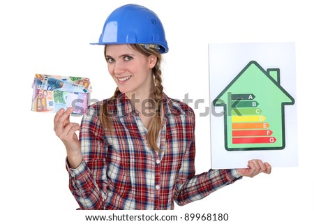 Woman holding money and energy rating card - stock photo
