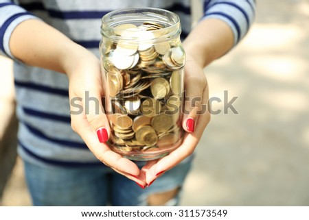 Woman holding money jar with coins outdoors - stock photo