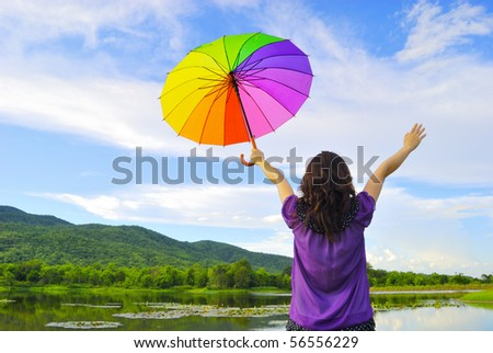 Woman  holding multicolored umbrella against the sunny sky