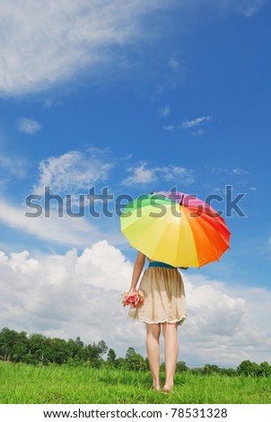 Woman holding multicolored umbrella and cloud sky