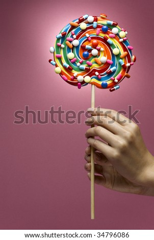 Woman holding multicoloured lollipop decorated with pills, close-up of hands