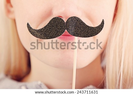 woman holding mustache on a stick in front of her face - stock photo