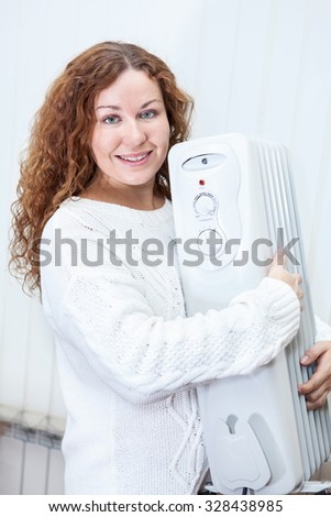 Woman holding new buying radiator in hands - stock photo