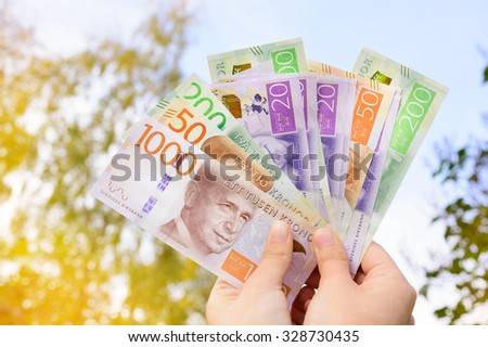 Woman holding new swedish bank notes, outdoors against trees. NOTE: the new 2015 model.