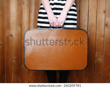 Woman holding old suitcase on wooden background - stock photo