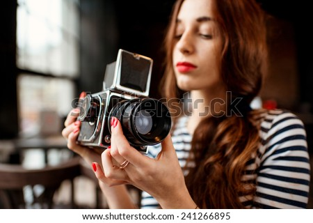 Woman holding old 6x6 frame photo camera - stock photo