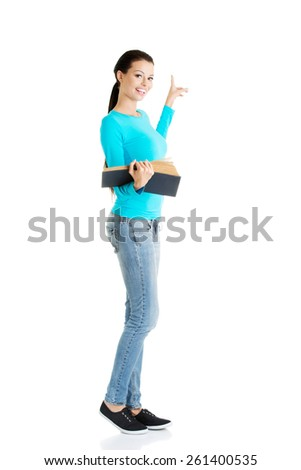 Woman holding open book and pointing on copyspace.