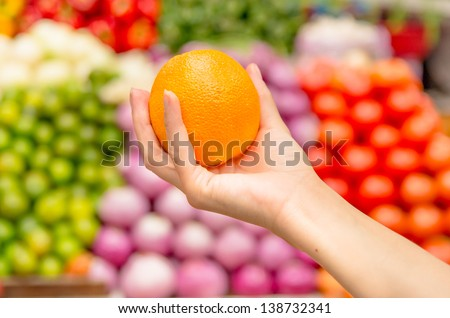 Woman holding orange   in supermarket with a background of lots of fruit - stock photo