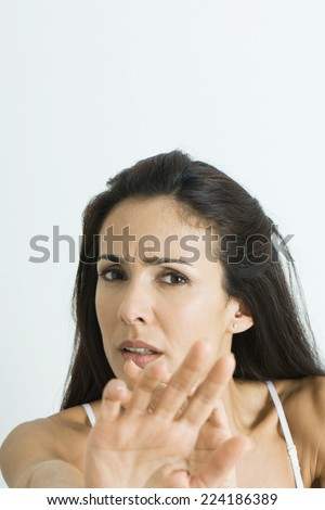 Woman holding out hands, frowning at camera, portrait - stock photo