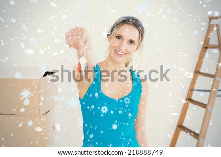 Woman holding out with key besides boxes in new house against snow - stock photo