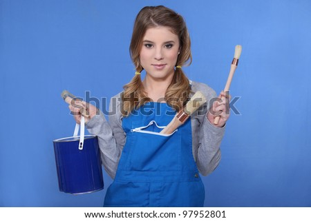 Woman holding paint brush and paint pot - stock photo