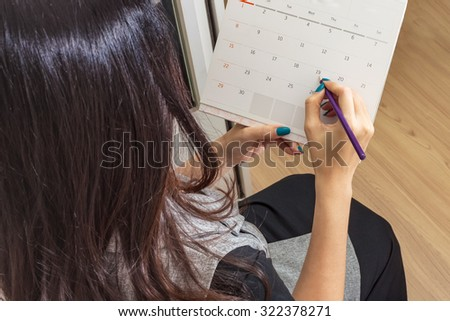 woman holding pencil on calendar for  making appointment  important day - stock photo