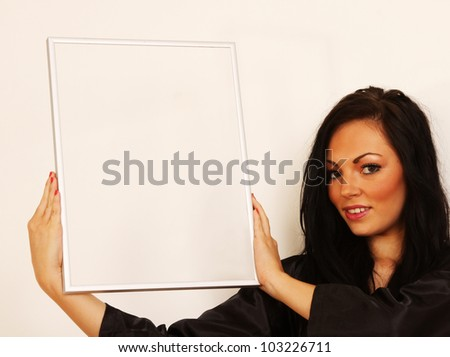 Woman holding picture frame that could used to as a placement for other images - stock photo