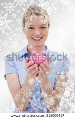 Woman holding piggy bank against snowflakes on silver - stock photo